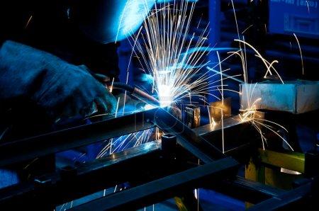 Photo pour Travail humain de soudage avec beaucoup d'étincelles dans une usine de métallurgie - image libre de droit