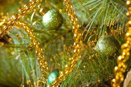 Beautiful green christmas decorations hanging on christmas tree with shiny glare