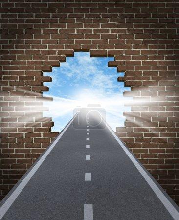 Photo pour Percer au concept d'occasion avec une route passant par un mur de briques cassées à une lumière briller de succès sur un fond de ciel comme une icône de l'entreprise et un sym - image libre de droit