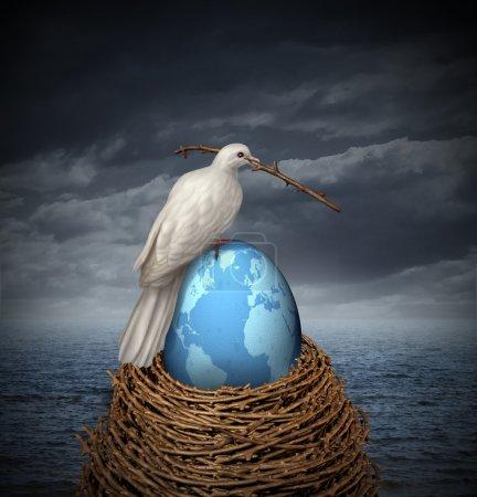 Photo pour Paix globale et espoir d'aucune guerre au Moyen-Orient et dans le reste de la planète avec une colombe blanche construisant un nid avec des brindilles et un œuf fragile avec la carte du monde sur un ciel nuageux et l'océan . - image libre de droit