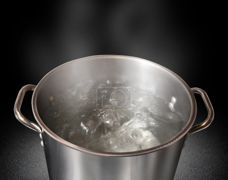 Boiling water in a kitchen pot as a symbol of cook...
