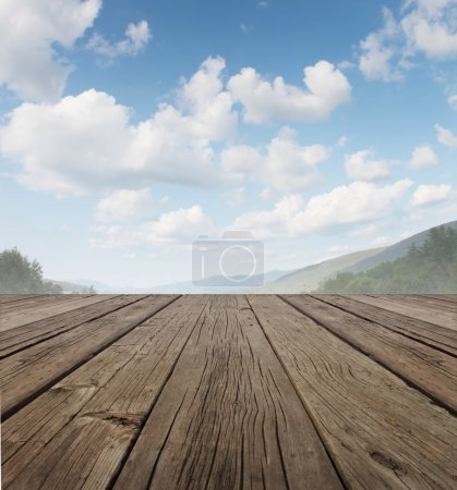 Photo for Wood deck as a tranquil old rustic country patio floor in perspective with a summer sky on a beautiful mountain range with forest trees as a symbol of travel and backyard living. - Royalty Free Image