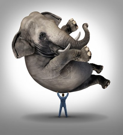 Photo for Leadership solutions business concept with a take charge businessman lifting a huge elephant as a symbol of a strong leader with courage and determination to release the power within and achieve what is impossible. - Royalty Free Image
