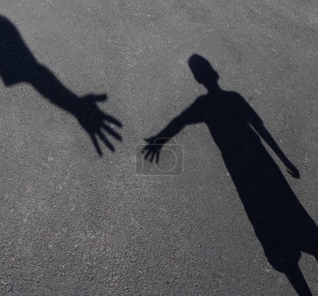 Photo pour Helping Hand with a shadow on pavement of an adult hand offering help or therapy to a child in need as a education concept of charity towards needy kids and teacher guidance to students who need tutoring . - image libre de droit