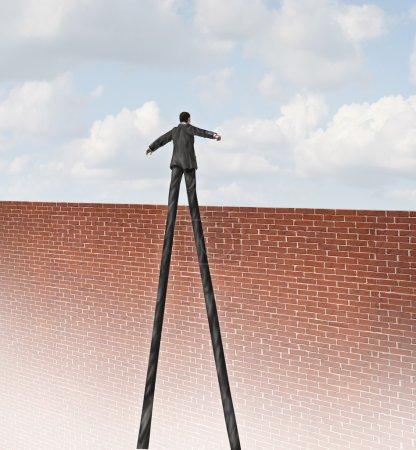 Photo pour Relever le défi et s'adapter à l'adversité en passant par le concept d'affaires de mur avec un homme d'affaires avec des jambes très longues pour atteindre le bord d'un mur de briques de hauteur comme une métaphore pour la liberté et de la réussite avec un chef qualifié. - image libre de droit