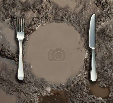 Photo for Food sanitation concept and global poverty symbol as a wet ground with a mud puddle of dirty water shaped as a dinner plate with a silver fork and knife as a metaphor for contamination health risk. - Royalty Free Image