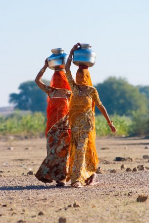 women lugging a water pot on their head