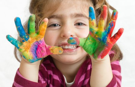 Photo for Portrait of a beautiful preschool girl with painted hands in background white - Royalty Free Image