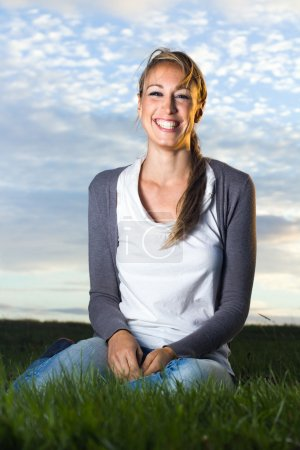 Beautiful laughing young woman sitting in field