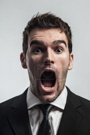 Photo pour Jeune homme hurlant surpris en regardant caméra. - image libre de droit