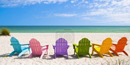 Photo pour Adirondack Beach Chaises sur une plage ensoleillée devant une maison de vacances Voyage - image libre de droit