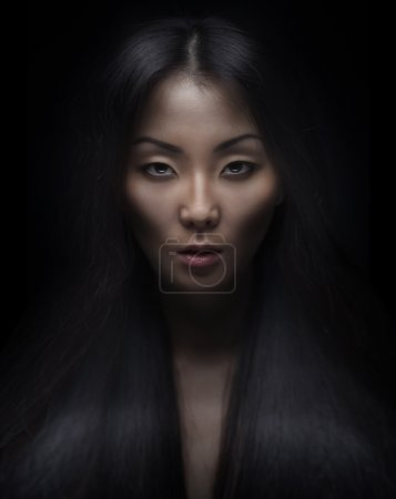 Photo for Beautiful young asian woman with long hair on dark background - Royalty Free Image