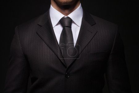 Businessman standing on dark background