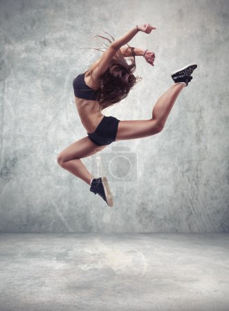 Young woman dancer with grunge wall background