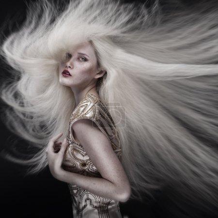 Photo pour Portrait d'une belle fille avec des volants de cheveux blonds isolée sur fond noir - image libre de droit