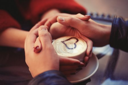 Four hands wrapped around a cup of coffee with hea...