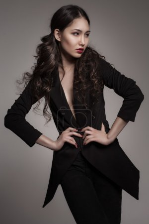 Fashion portrait of young asian woman on dark grad...