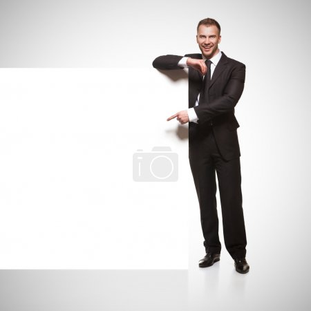 Photo for Portrait of happy smiling young business man showing blank signboard isolated on grey gradient background - Royalty Free Image