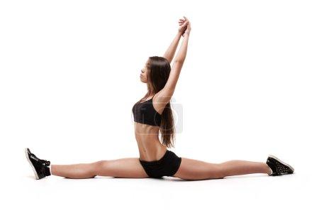 Portrait of girl gymnasts, sitting on the splits