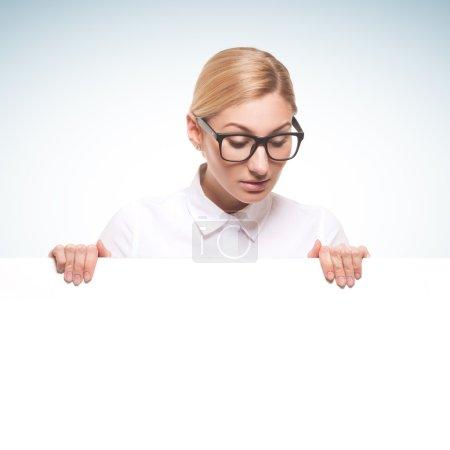 Photo pour Belle femme d'affaires portant des lunettes tenant un panneau blanc isolé sur fond blanc - image libre de droit