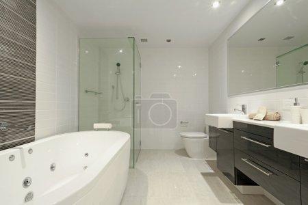 Photo pour Élégante salle de bain avec deux lavabos, miroir, douche, WC et baignoire ronde . - image libre de droit