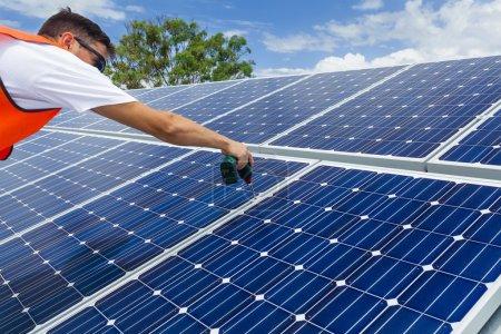 Foto de Joven técnico instalando paneles solares en el techo de fábrica - Imagen libre de derechos