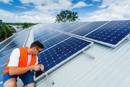 Foto de Joven técnico instalar paneles solares en el techo de fábrica - Imagen libre de derechos