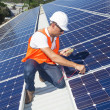 Young technician checking solar panels on factory ...