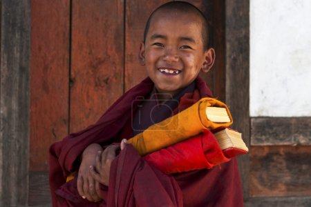 Little Buddhist monk with prayer books in Bhutan