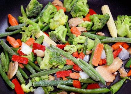 Foto de Surtido de verduras en una sartén antiadherente. habas, zanahorias, pimientos, maíz y más. - Imagen libre de derechos