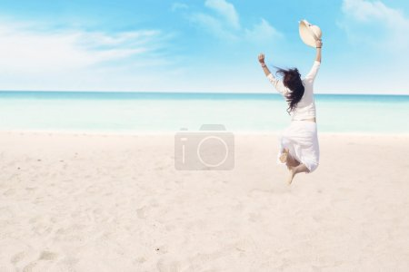 Photo for Happy carefree woman jumping on beach celebrating her freedom - Royalty Free Image