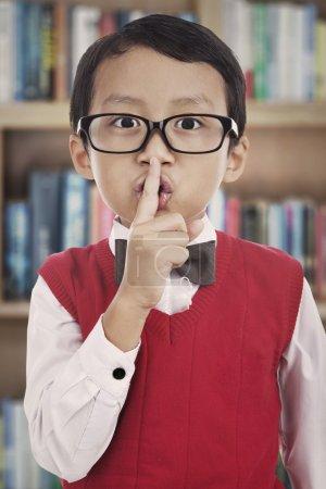 Photo pour Mignon asiatique élémentaire élève avec son doigt sur sa bouche, étouffant. tourné dans la bibliothèque - image libre de droit