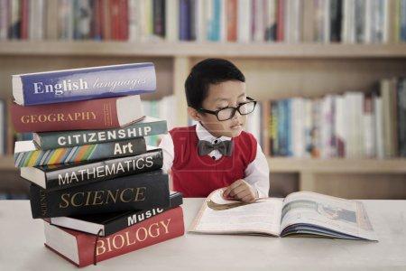 Photo pour Portrait de petit élève asiatique du primaire étudiant en lisant des livres de leçons. tourné dans la bibliothèque - image libre de droit