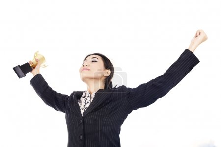 Businesswoman celebrating with trophy isolated over white