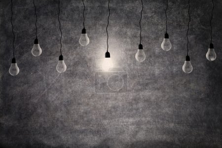 Photo for Bright idea concept: a glowing light bulb in front of empty blackboard with copy space - Royalty Free Image