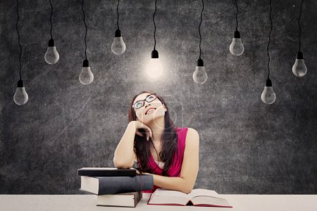 Photo for Portrait of smart female college student with books and bright light bulb above her head as a symbol of bright ideas - Royalty Free Image