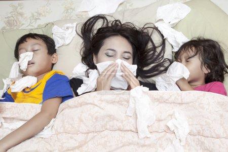 Photo pour La famille est allongée sur un lit à cause de la grippe en hiver - image libre de droit
