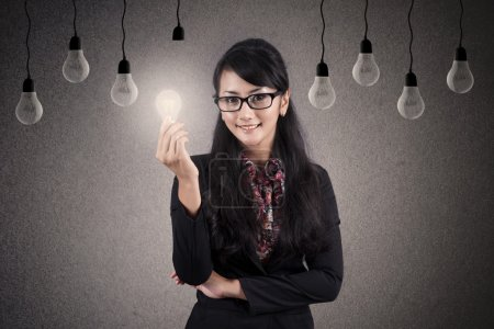 Photo for Beautiful Asian Businesswoman with glasses holds bright lightbulb - Royalty Free Image