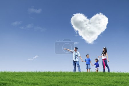 Photo for Happy family walking in the park with cloud of love in the sky - Royalty Free Image
