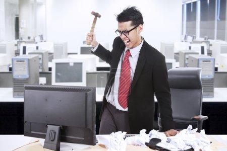 Photo pour En colère, homme d'affaires s'apprête à jeter un marteau à son ordinateur au bureau - image libre de droit