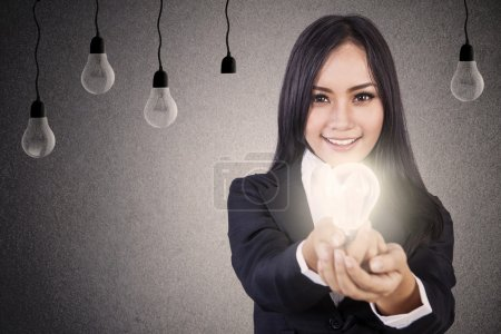 Photo for Businesswoman giving you a bright light bulb symbolising bright idea - Royalty Free Image