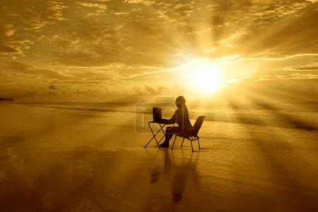 Photo pour Jeune fille est assise avec son ordinateur portable sous le beau coucher de soleil sur la plage - image libre de droit