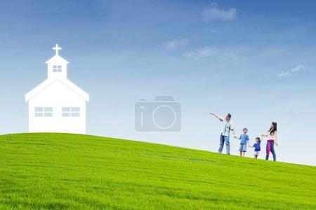 Photo pour La famille chrétienne marche jusqu'à l'église au sommet d'une colline - image libre de droit