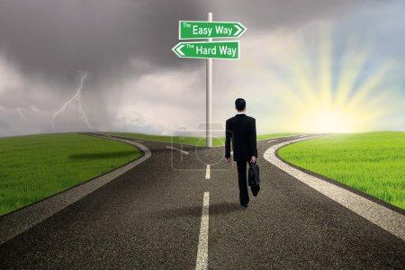Photo pour Homme d'affaires marche sur la voie de manière simple avec fond orageux - image libre de droit