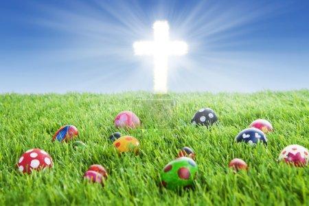 Photo pour Image d'œufs de Pâques colorés pondant sur l'herbe avec une croix lumineuse - image libre de droit