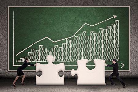 Photo pour Deux entreprises joignant puzzle manquant ensemble sur fond de diagramme à barres de profit - image libre de droit