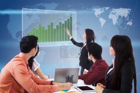 Photo pour Réunion d'affaires avec présentation et diagramme à barres de profit sur fond de carte bleue du monde - image libre de droit