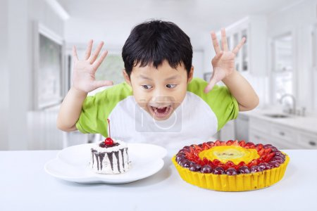 Excited boy eating dessert at home
