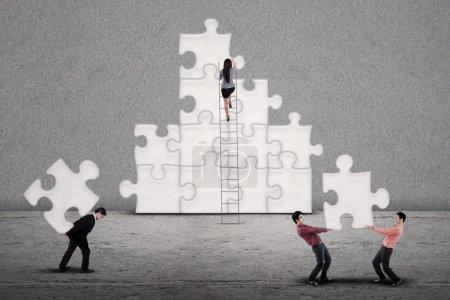 Photo pour Business team building puzzles ensemble sur fond gris - image libre de droit
