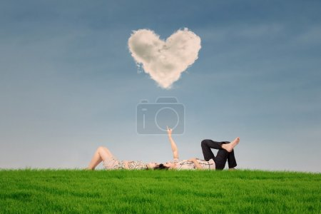 Couple enjoy holiday under heart cloud in park